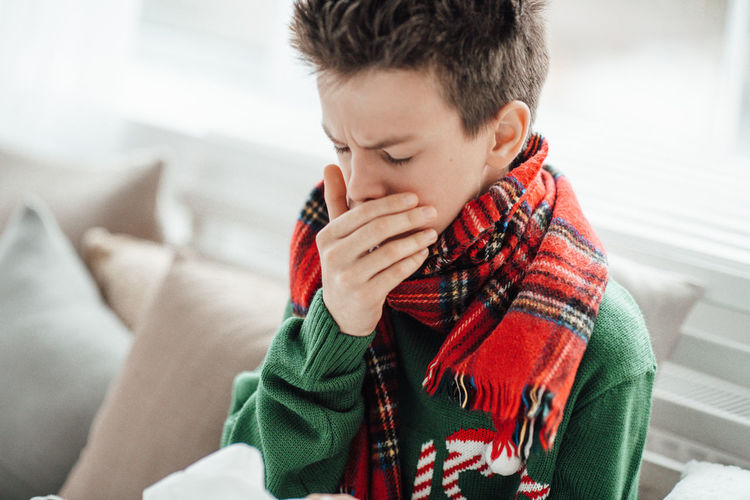 Close-up of boy sneezing at home