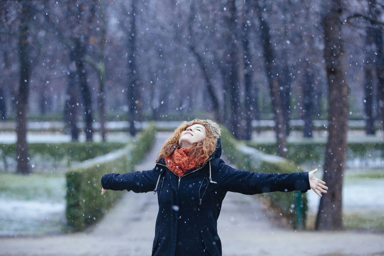 Close-up of woman standing on snow covered tree during winter