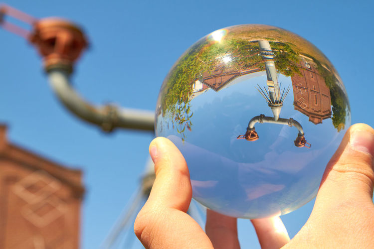 Protego cap Protego Protego Cap Sphere Architecture Body Part Building Building Exterior Built Structure Day Finger Focus On Foreground Glass Glass Sphere Hand Holding Human Body Part Human Hand Lifestyles Nature One Person Outdoors Real People Sky Sphere Sunlight
