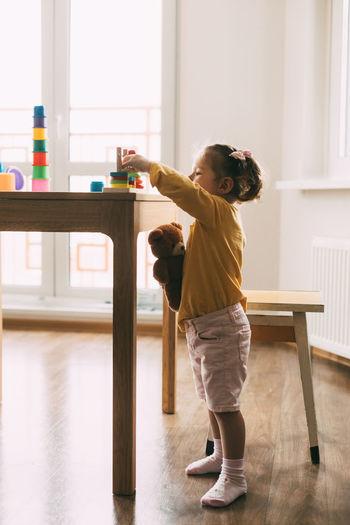 A little girl sorts colorful geometric shapes. development of motor skills.