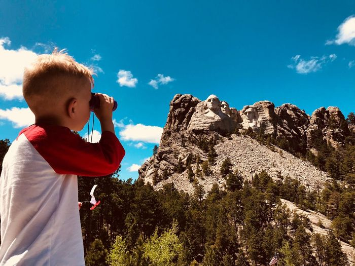 Boy Looking Through Binoculars Towards Mount Rushmore National Memorial