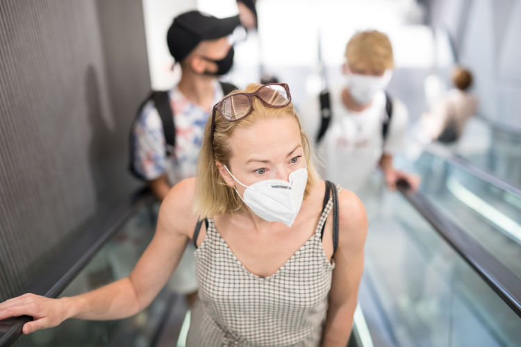 High angle view of woman wearing flu mask standing at mall