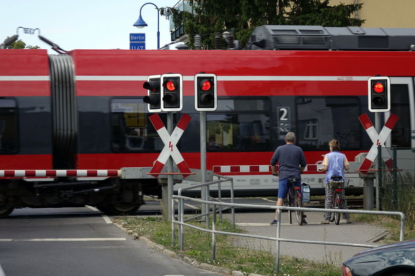 Level Crossing Architecture City Crossing Day Land Vehicle Men Mode Of Transportation Nature Not Recognisable Person Outdoors People Public Transportation Rail Transportation Railroad Track Real People Rear View Red Track Train Train - Vehicle Transportation Travel