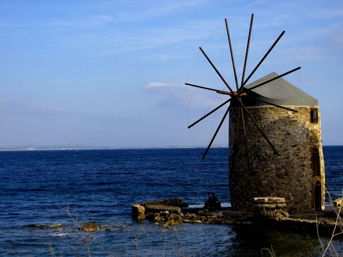 Traditional Windmill By Sea Against Sky