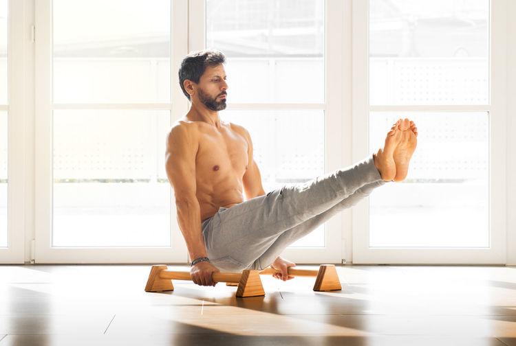 Shirtless man exercising by window in gym