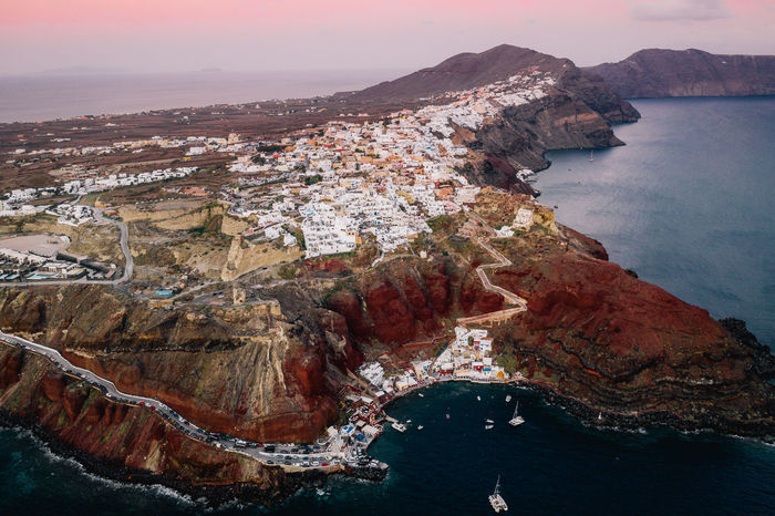 The infamous Oia, Santorini is situated atop some incredible red cliffs that lead into the ocean. Water Sea Beauty In Nature Rock Formation Scenics - Nature Mountain Rock - Object Nature Sky No People High Angle View Tranquil Scene Tranquility Architecture Day Outdoors Formation Week On Eyeem Santorini Santorini Greece Greece Dji Mavic Pro 2 Aerial View
