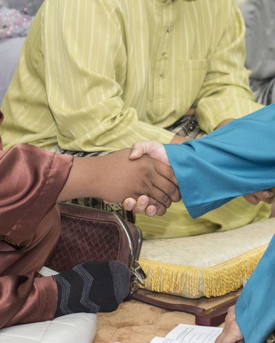 Cropped Image Of People Shaking Hands With Man Sitting In Background