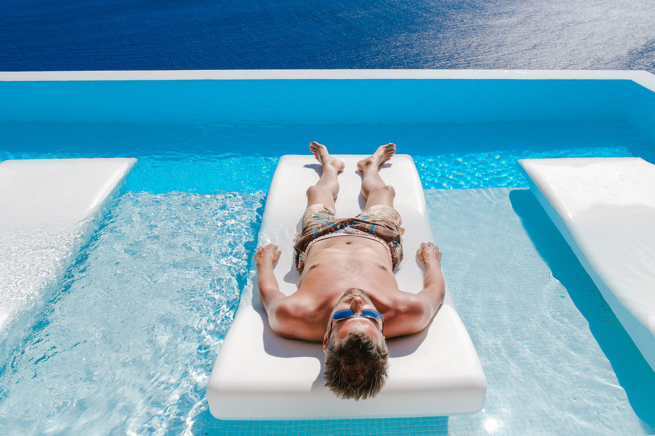 High Angle View Of Young Man Lying On Lounge Chair In Swimming Pool