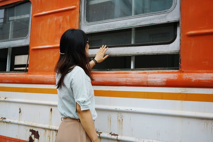 Side view of woman standing by train at station