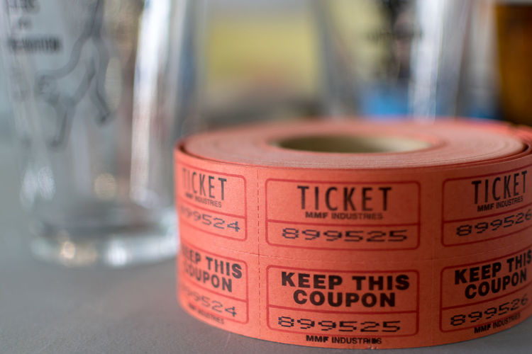 roll of raffle tickets in front of glasses Close-up Communication Day Focus On Foreground Indoors  No People Raffle Red Table Text