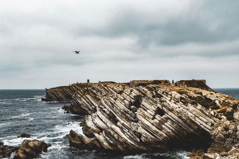 Scenic view of rocky coastline in sea against sky