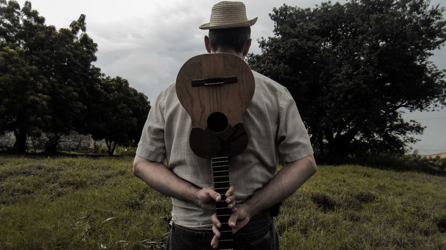 Rear view of man holding ukulele while standing on grassy field