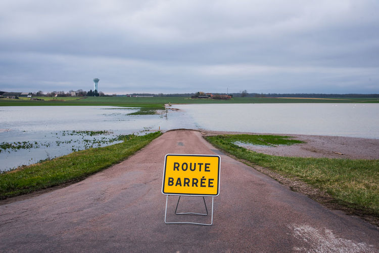 Rural Scene Field Countryside Landscape Road Flood Flooded Flooded Road Way Closed Closed Road Interdiction Horizon Over Water Road Sign Traffic Arrow Sign Do Not Enter Sign Stop Sign Directional Sign One Way Calm Seascape Information Warning Signboard Capital Letter Western Script