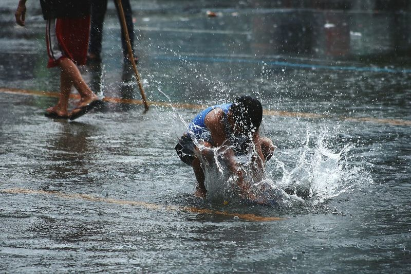 Boy playing with water on road