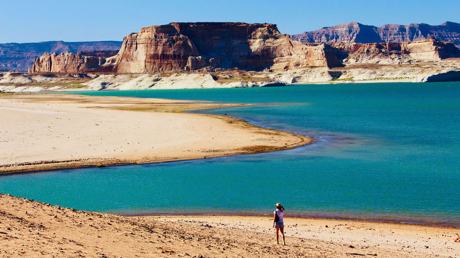 Rear view of man standing by lake powell