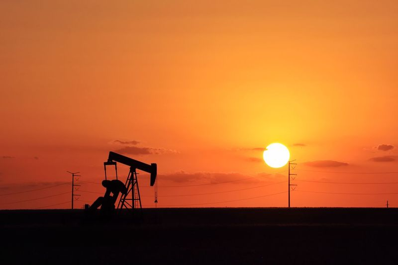 Permian Basin sunset with hot sun and pump jack silhouette Texas Pump Jack Desert Heat Silhouettes Texas Sky Texas Energy Texas Landscape Oil And Gas Industry Fossil Fuel Midland, TX Petroleum Industry Silhouette Sunset Sky Orange Color Beauty In Nature Scenics - Nature Horizon Nature Sun Copy Space