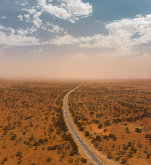 Drone aerial of a highway through the landscape of the outback with a massive dust storm on horizon