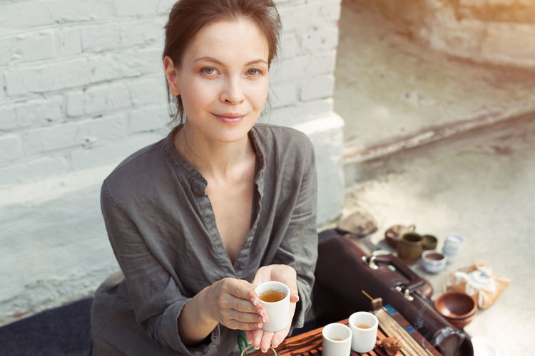 Portrait of woman holding tea cup against brick wall