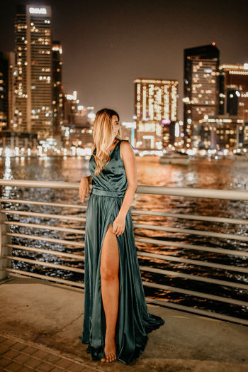 Full length of woman standing by modern buildings in city at night