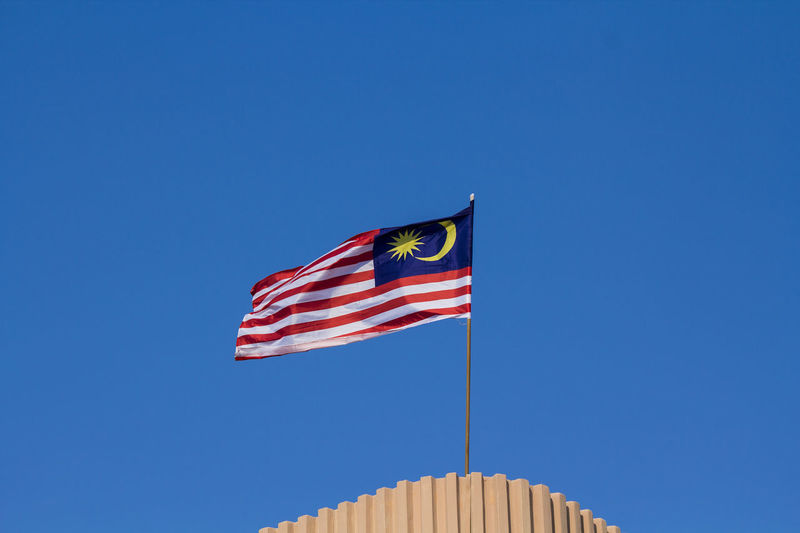 Low Angle View Of Malaysian Flag Against Clear Blue Sky