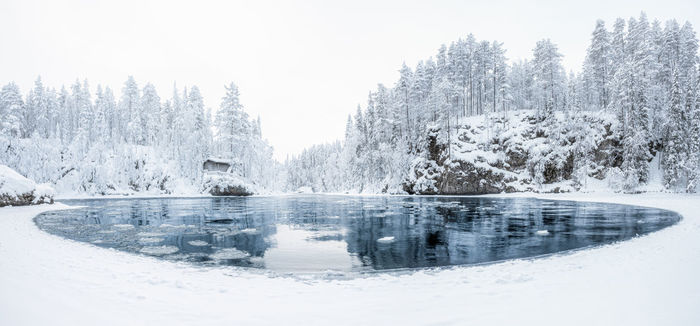 A river by snow covered trees against sky