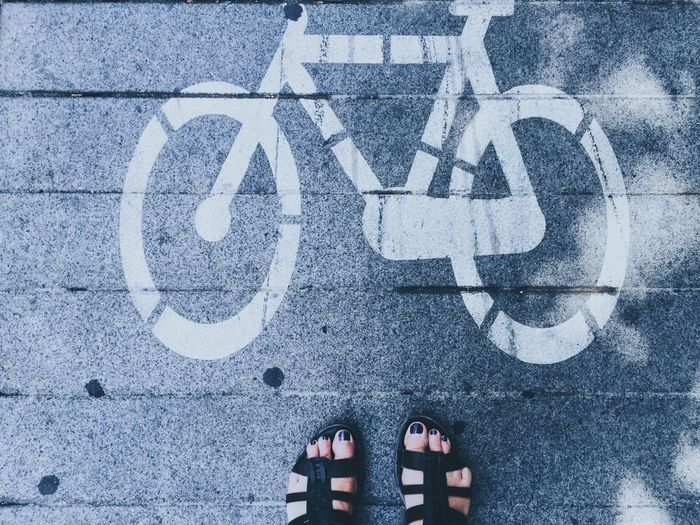 Low Section Of Woman Standing By Bicycle Sign On Road