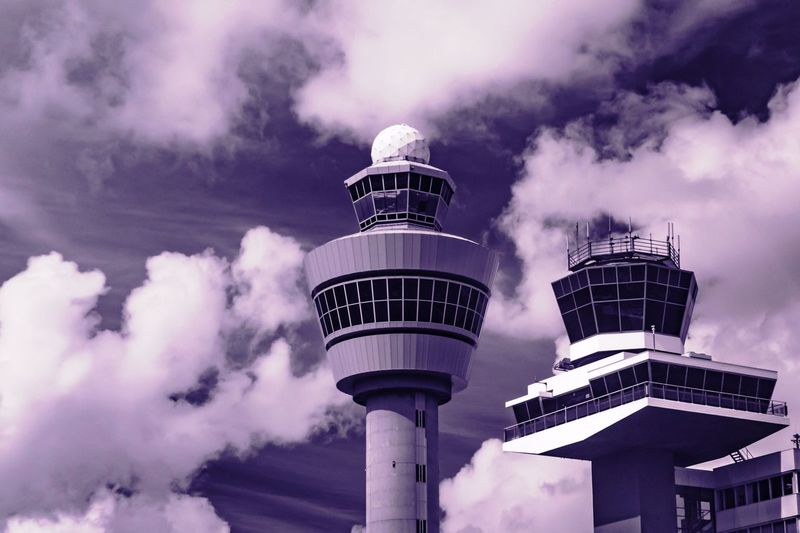 Low angle view of air traffic control tower against cloudy sky