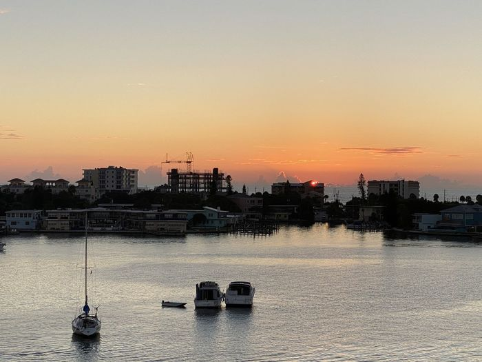 Boats in sea by buildings against sky during sunset