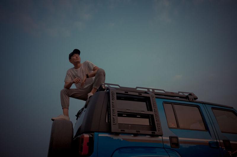 Full length of man sitting against sky
