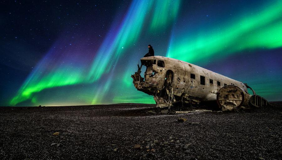 Abandoned Airplane On Land Against Aurora Borealis At Night