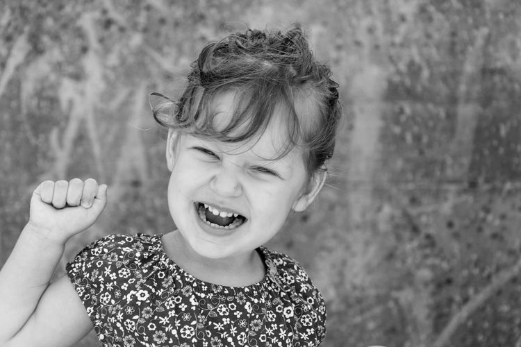 Close-up portrait of happy girl against wall