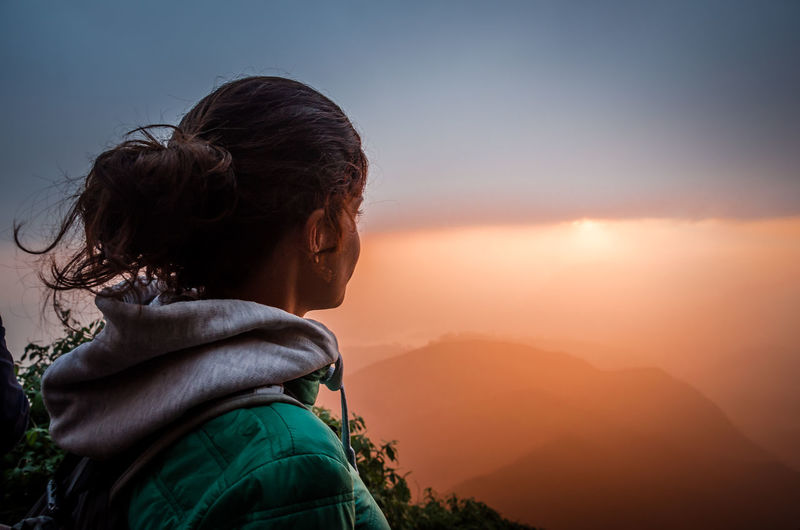 Woman Looking At Mountains Against Sky During Foggy Sunrise