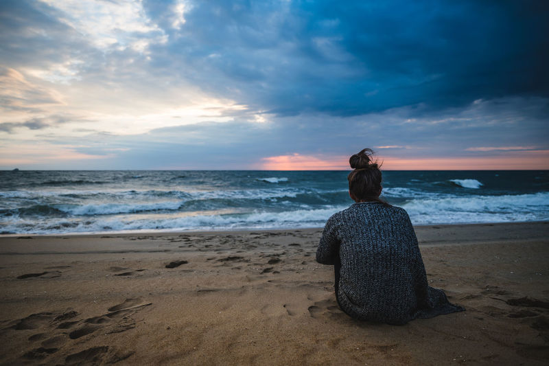 Rear view of woman looking at sea against sunrise sky on the beach