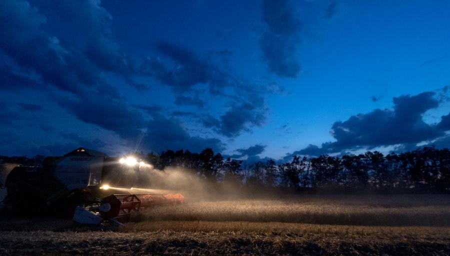 Illuminated machinery harvesting plants on field