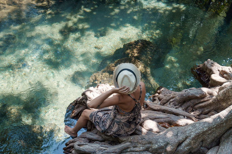 High angle view of woman relaxing next to crystal clear water