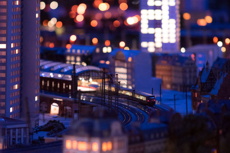 Tilt-shift image of train on railroad tracks in illuminated city