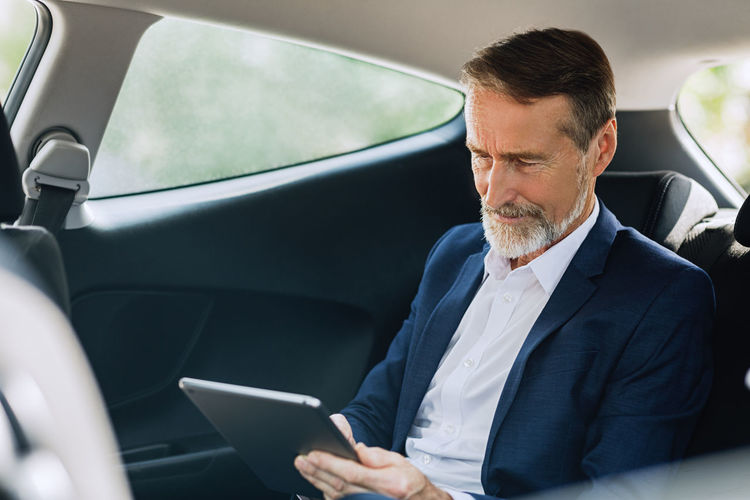 Man using digital tablet while sitting in car