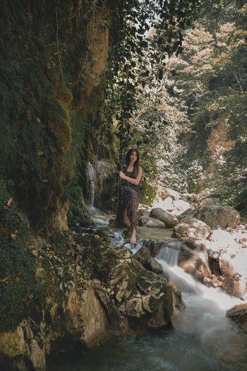 Portrait of woman sitting on swing against waterfall