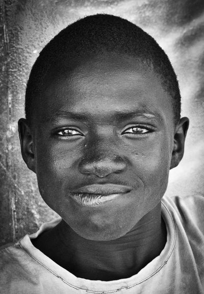 Portrait of a talibé. Poor families in Senegal sometimes entrust their boys to unscrupulous, itinerant marabouts, who then force the children to beg for money. Failure to deliver will often result in beatings. When I gave a copy of the photo to the boy, he couldn't believe it, and ran off whooping for joy to show his friends. Africa Child Abuse Close-up Composition Confidence  Contemplation Exploitation Front View Head And Shoulders Headshot Human Face Looking At Camera Ngor Portrait Reflection Senegal Serious Talibé Uncertain Young Adult Youth Of Today