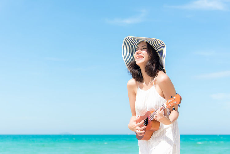 Young woman wearing hat against sea against sky