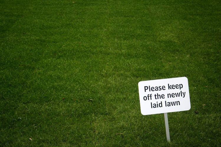 Close-up of information sign on grass