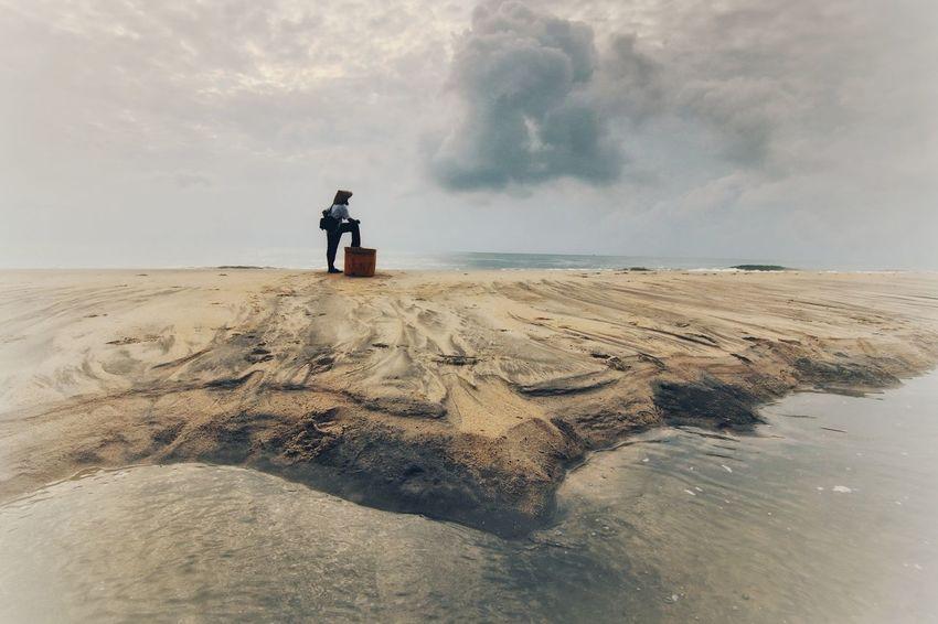 A fisherman at the beach Sand Dune Full Length Beach Sand Adventure Men Sea Headwear Water Lightning Power In Nature Dramatic Sky Atmospheric Mood