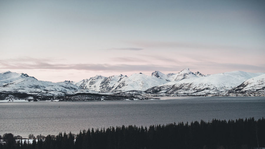 Scenic view of lake against snowcapped mountains during sunset