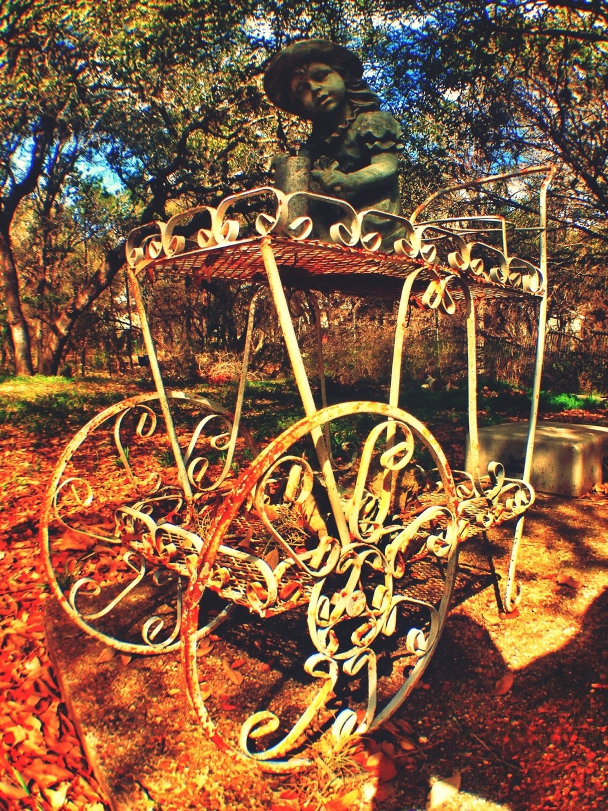 wheel, bicycle, metal, rusty, old, sunlight, built structure, day, no people, tree, art and craft, metallic, architecture, outdoors, art, abandoned, creativity, wall - building feature, close-up, wood - material