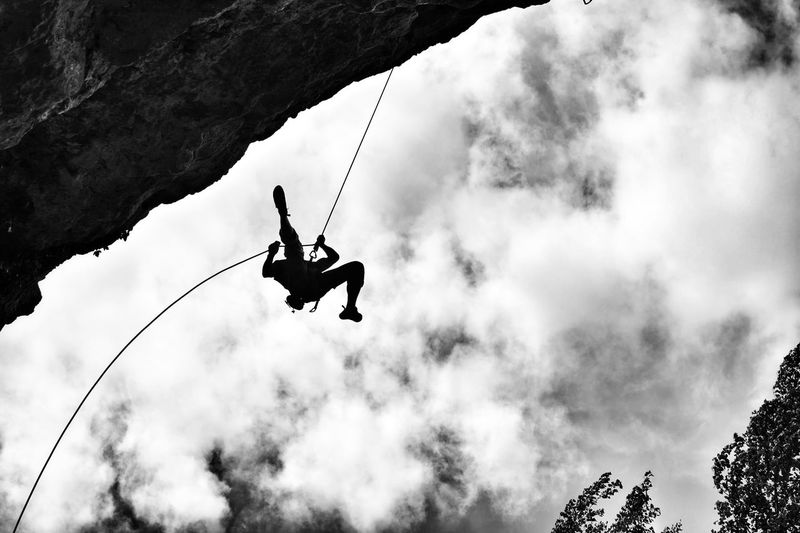 Low angle view of man hanging from rope by mountain