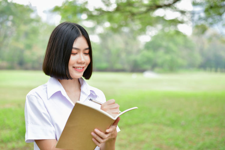 Smiling Young Woman Writing In Book While Standing On Field