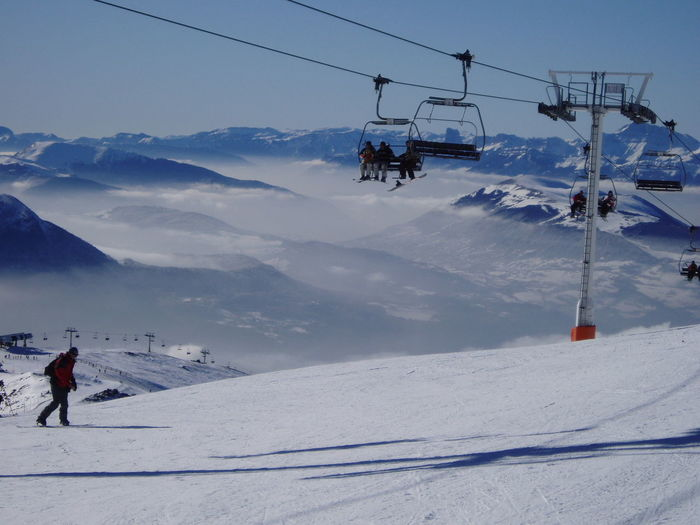 People Enjoying In Ski Lift Over Snow Covered Mountain