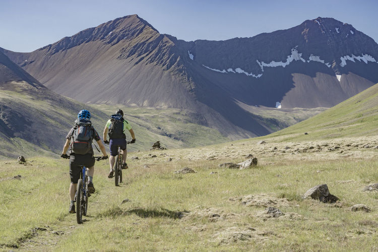 Rear View Of People Riding Bicycle On Mountain