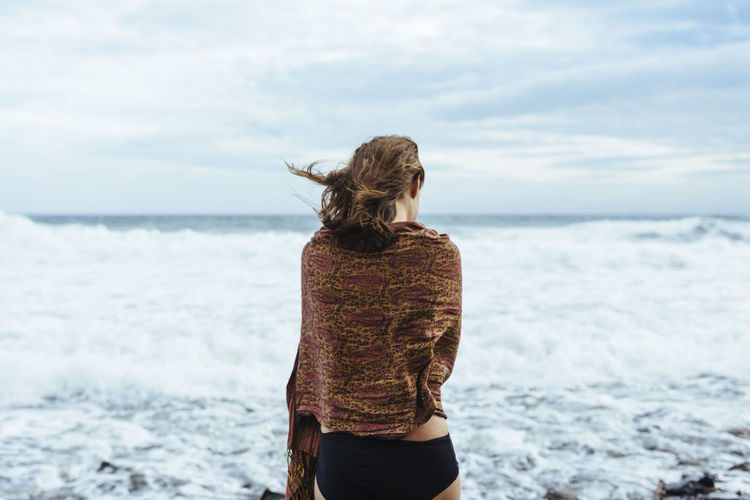 Young woman facing stormy sea Beach Beauty In Nature Day Horizon Over Water Leisure Activity Lifestyles Nature One Person Outdoors People Real People Rear View Scenics Sea Sky Standing Water Wave Women