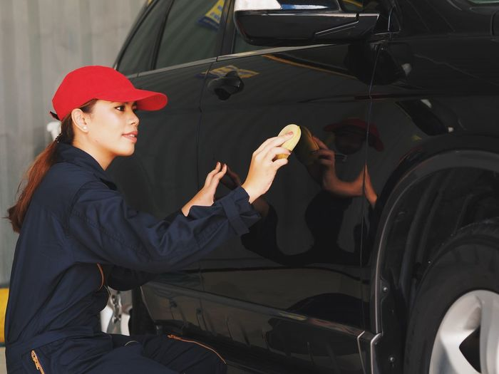 Side View Of Young Woman Cleaning Car In Garage